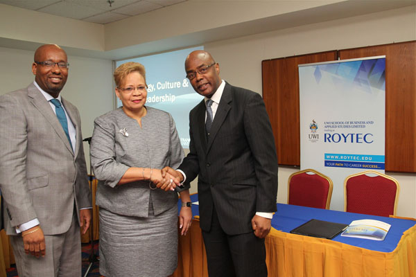 UWI St. Augustine Campus Registrar, Mr. Richard Saunders congratulates UWI-ROYTEC Executive Leader, Ms. Wendy Augustus
